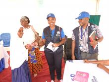 WHO Staff handing over vaccination card to the vaccinated girl