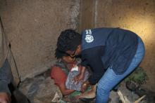 WHO staff helps mother wrap baby in warm blanket at Gedeb IDP site