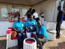 WHO staff enjoy the comfort of a chair made using ARV bottles by one of the partners at the WHO/UNAIDS stall
