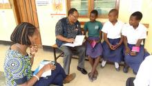 WHO staff interacting with the girls after vaccination