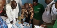The Chief Medical Officer of Juba County, Dr. Justin Nyoma, demonstrates the use of an EWARS mobile phone during a supervisory visit to a health facility