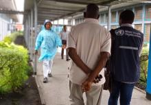 Dr. Ramses Kalumbi walks with the father of a suspected case