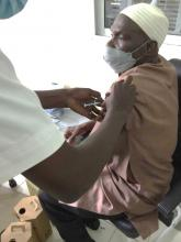 Mr. Sulayman Manneh, happily receiving the COVAX vaccine
