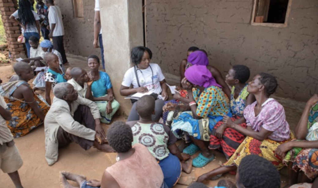 At the Maluwa camp health outreach clinic, a doctor attends to the many clients waiting.